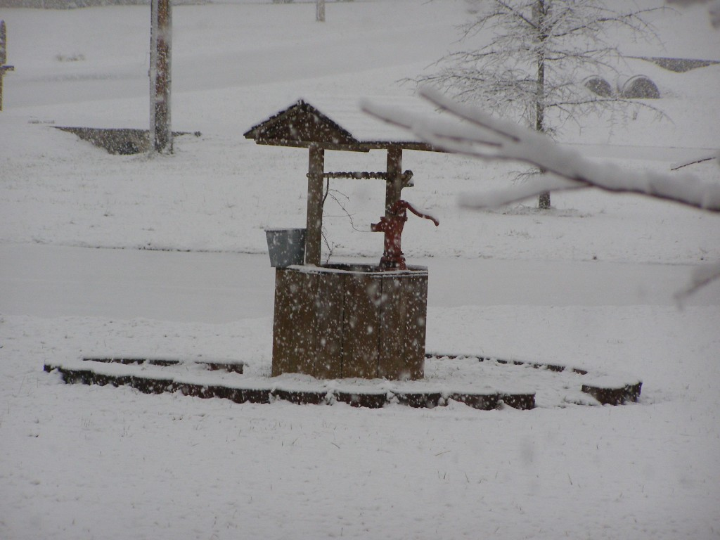 Our neighbor's faux well covered in snow with falling snowflakes in the foreground