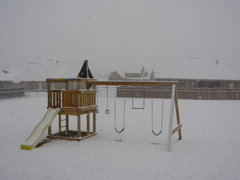 Our back yard and our kids' swing set covered in snow